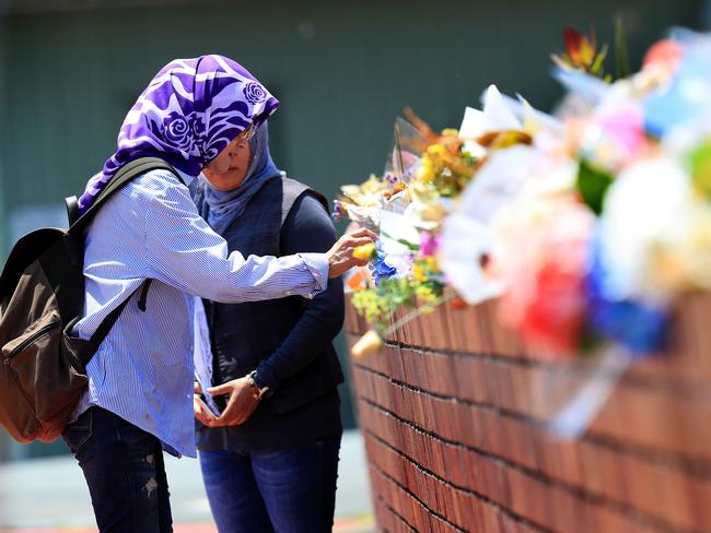 Visitors add to the floral tribute outside Dreamworld after the tragedy. Picture: Adam Head