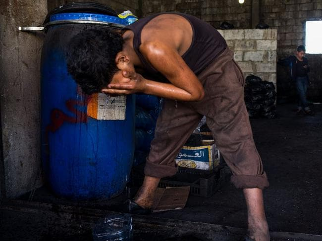 Anas Ezza washes his face after finishing work at the charcoal shop in Bebnine. Like his friends, he misses school. Picture: UNHCR / Andrew McConnell