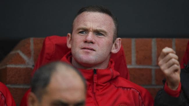 Manchester United's English striker Wayne Rooney sits on the bench.