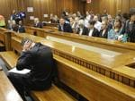 Oscar Pistorius blocks his ears inside the high court on the second day of his trial. Picture: AP Photo/Kim Ludbrook, Pool