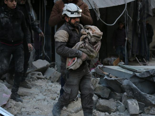 Civilian casualties ... A Syrian Civil Defence worker carries a child wrapped in a blanket over the rubble in Deir Ezzor. Picture: AFP