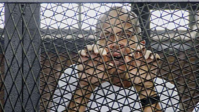 Caged .... Peter Greste, appears in a defendants' cage in a courthouse near Tora prison in Cairo, Egypt. Picture: Hamada Elrasam