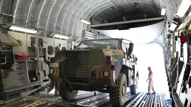 Our role in Afghanistan ... the crew of a C-17 RAAF aircraft load an Army Bushmaster vehicle onto the massive cargo plane at Kandahar airfield in Afghanistan. Picture: Gary Ramage
