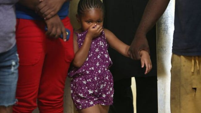 Unusual find ... Zykerra Bogan, 4, reacts as she watches Ken Owens skin and harvest the meat from the Stokes alligator last week. Picture: Sharon Steinmann/al.com