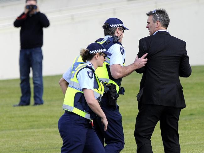 Anti-racing protester Elio Celotto is escorted out of the Sandown Races by police.