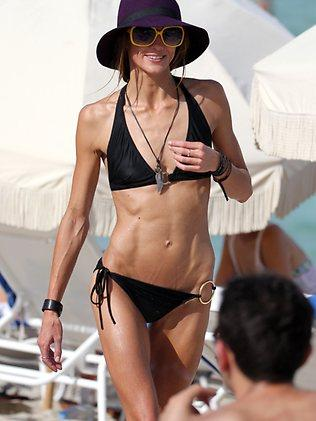 Australian actress Sharni Vinson in a black bikini and large purple hat at the beach in Miami Beach. Picture: Splash