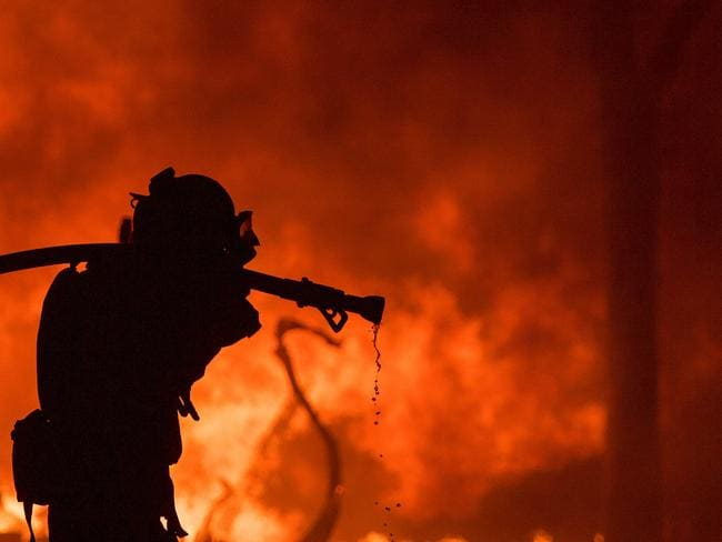 A firefighter pulls a hose in front of a burning house in the Napa wine region of California. Picture: AFP