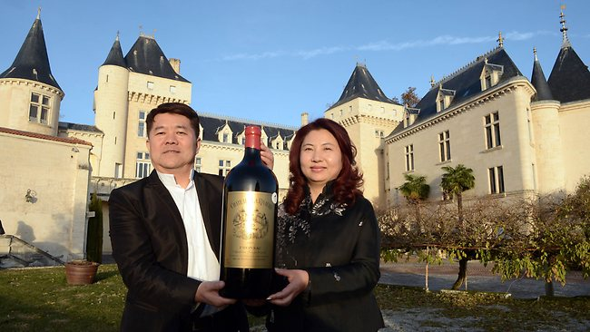 Chopper crash...Chinese billionaire Lam Kok (L) and his wife pose for a photograph in front of the Chateau de La Riviere, France. Kok and his 12-year-old son died in a helicopter crash while flying over their new vineyard. Picture: AFP