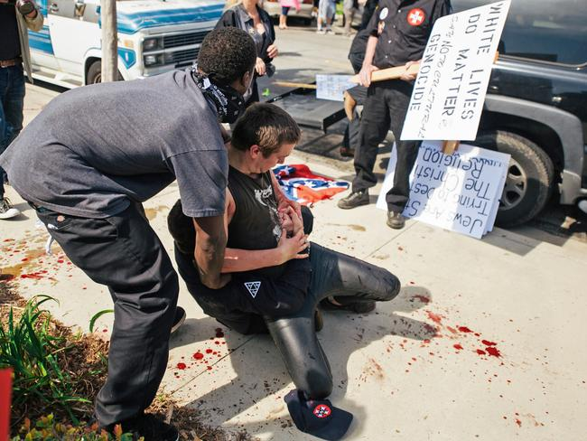 Two counter-protesters scuffling with a KKK member in Anaheim on Saturday. Picture: Eric Hood/OC Weekly via AP