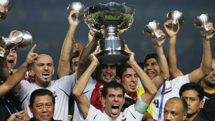 Player Younis Khalef holding Asian Cup trophy with teammates after win. Soccer - Iraq vs Saudi Arabia Asian Cup final match in Jakarta, Indonesia 29 Jul 2007. /Soccer/International/matches