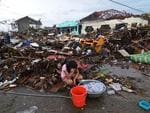 A girl pauses while washing clothes amongst the debris in an area devastated by Typhoon Haiyan in Leyte, Philippines.Picture: Getty Images