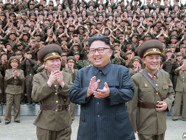 Kim Jong-un poses with officers and troops outside the KPA Strategic Force HQ after being 'briefed' on plans to launch missiles towards Guam.