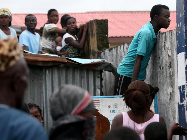 Unrest ... a crowd looks over the wall into an Ebola isolation centre before pushing into the facility in the West Point slum. Picture: Getty