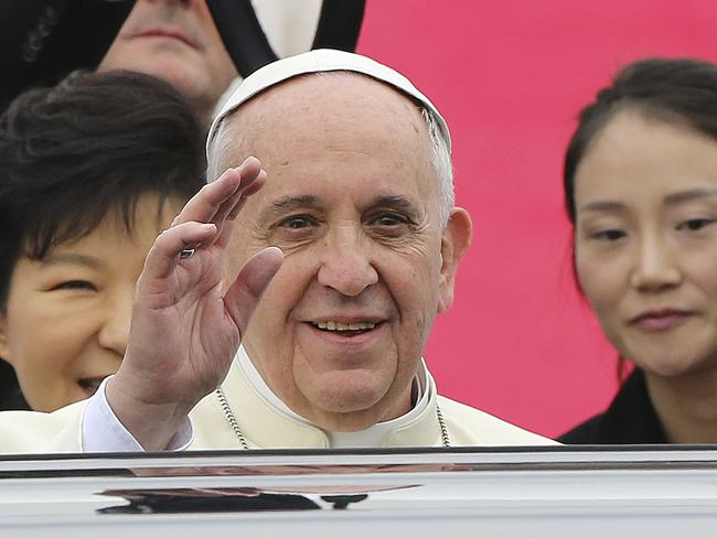 Greattings ... Pope Francis waves upon his arrival at Seoul Air Base as South Korean President Park Geun-hye looks on in Seongnam. Picture: AP