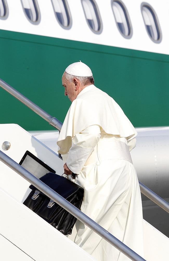 Baggage Handler ... Pope Francis boards a flight at Rome's Fiumicino international airport carrying his own luggage. Picture: AP/RICCARDO DE LUCA.