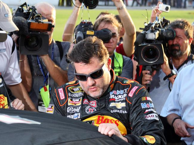 Tony Stewart climbs into his car to start a NASCAR Sprint Cup auto race at Atlanta Motor Speedway.