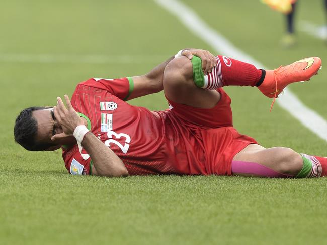 Iran defender Mehrdad Pooladi clutches agonisingly at a sock which has pulled one of the hairs in his shin. Ooooh, that's gotta hurt.