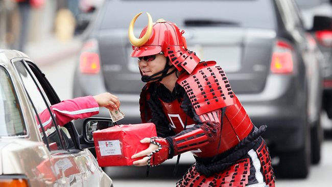 Japanese-American volunteer Darin Furukawa dressed in a traditional Japanese Samurai outfit, collects donations during an all day Red Cross fundraiser to support the Japanese earthquake relief efforts outside Los Angeles City Hall yesterday. Picture: AP