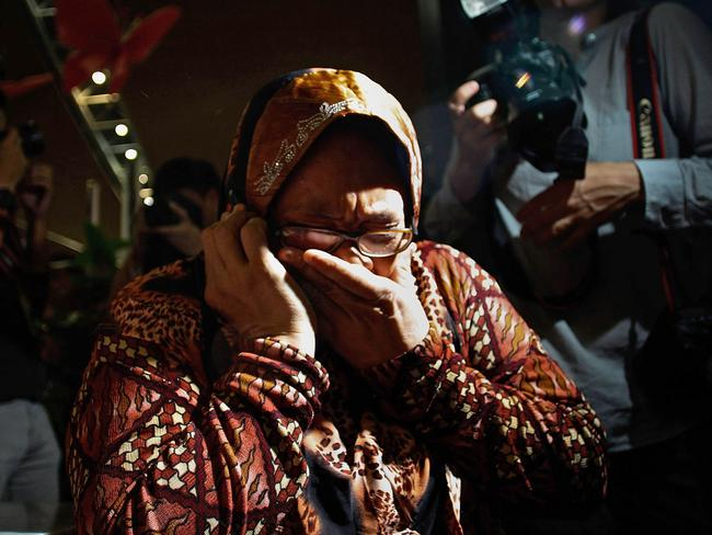 A family member cries as she receives the news of the ill fated flight MH17 on the phone. Picture: Rahman Roslan