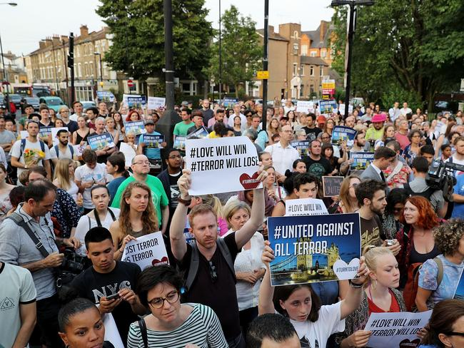 People hold up signs saying 'united against terror' as they attend a vigil outside Finsbury Park Mosque. Picture: Dan Kitwood/Getty Images