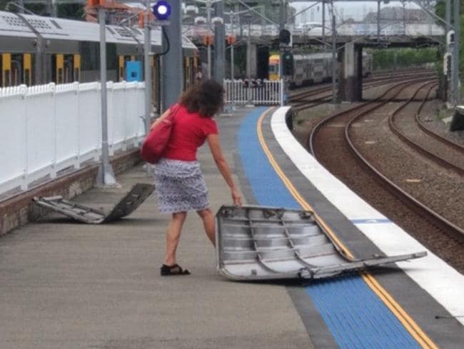 A woman drags a piece of train that was blown off at Burwood Station. Picture: Twitter