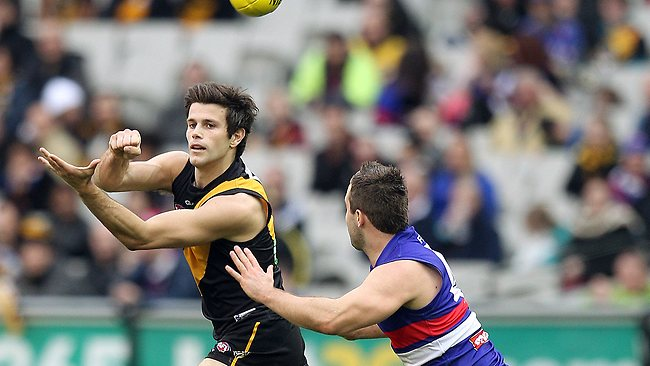 Richmond v Western Bulldogs. MCG. Trent Cotchin handballs over Andrew Hooper Picture: Michael Klein