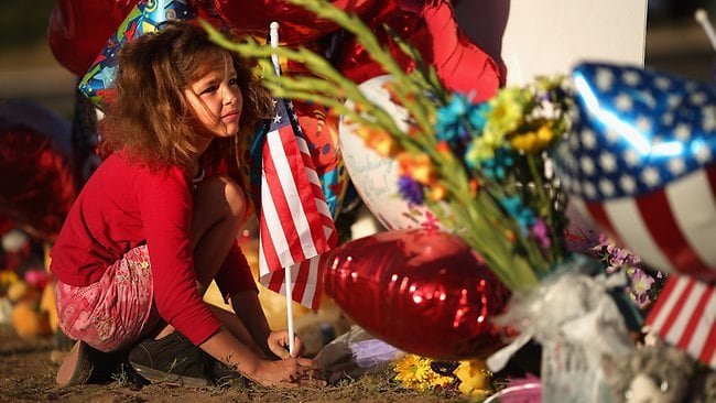 AURORA, CO - JULY 22: Seven-year-old Serenity Brydon visits a makeshift memorial to the vicitims of last weekend's mass shooting at the Century 16 movie theater July 22, 2012 in Aurora, Colorado. Police in Aurora, a suburb of Denver, say they have James Holmes, 24, in custody after he killed 12 people and injured 59 during a midnight screening of 'The Dark Knight Rises' last Friday. Chip Somodevilla/Getty Images/AFP== FOR NEWSPAPERS, INTERNET, TELCOS & TELEVISION USE ONLY ==