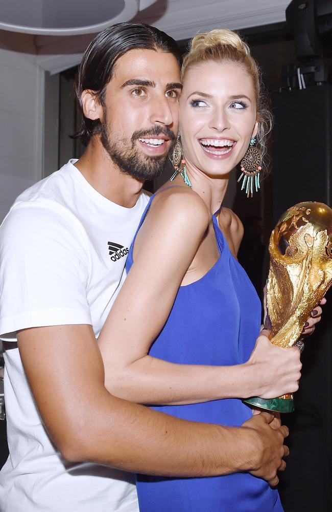 Sami Khedira of Germany and girlfriend Lena Gercke pose with the World Cup trophy.