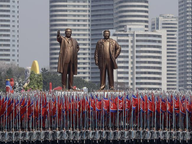 University students carry North Korean national flags in front of two bronze statues of the late leaders Kim Ii-sung and Kim Jong-il during Saturday's military parade. Picture: Wong Maye-E/AP
