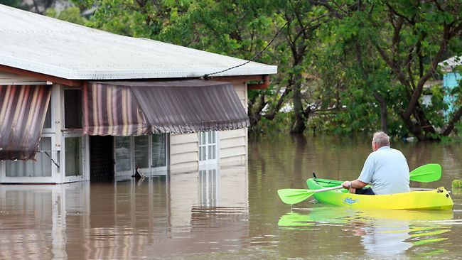 DAMAGE CLAIM: A Bundaberg resident inspects his flooded home by kayak. Picture: AFP
