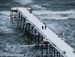 A couple walk along the snow covered pier at the beach on February 27, 2018 in Saltburn-By-The-Sea, England. A cold weather front from Russia brings snow across much of the UK with further snow showers pushing in from the east. The cold weather is set to continue through the week with frequent snow showers in the east of England and along the coast in the south-west. Picture: Getty Images