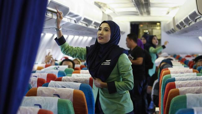 Female Rayani Air flight crew adhere to Islamic dress codes on all flights. Picture: AP Photo/Joshua Paul