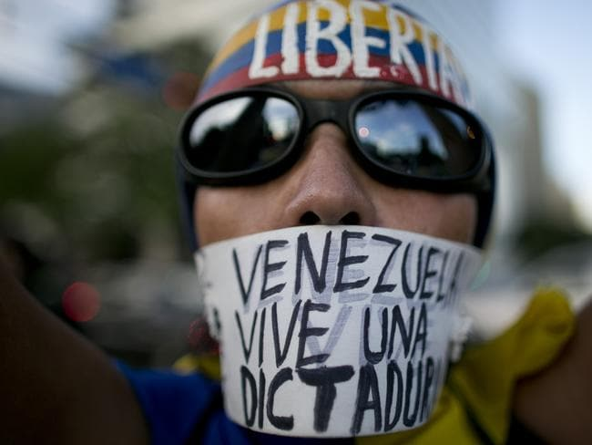 "A woman wears a banner over her mouth with a message that reads in Spanish: ""Venezuela lives in a dictatorship"" during a protest, in Caracas. Picture: AP"