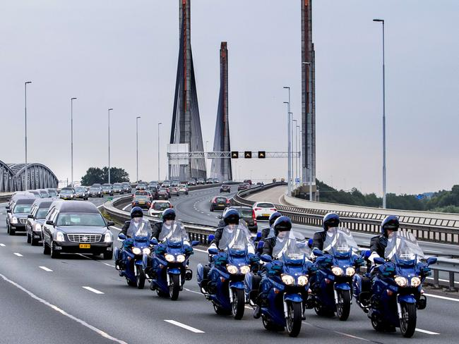 A nation in mourning ... funeral hearses depart Eindhoven air base on July 25. Picture: Vincent Jannink