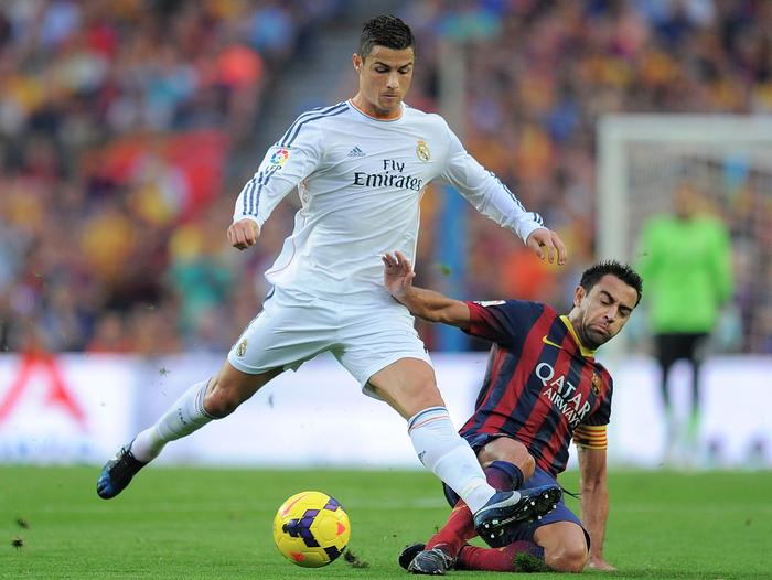 Cristiano Ronaldo of Real Madrid CF (L) is tackled by Xavi Hernandez of FC Barcelona.