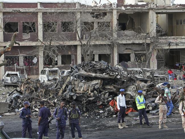 Somali security forces and others gather and search for bodies near destroyed buildings at the scene of Saturday's blast, in Mogadishu on Sunday. Picture: AP