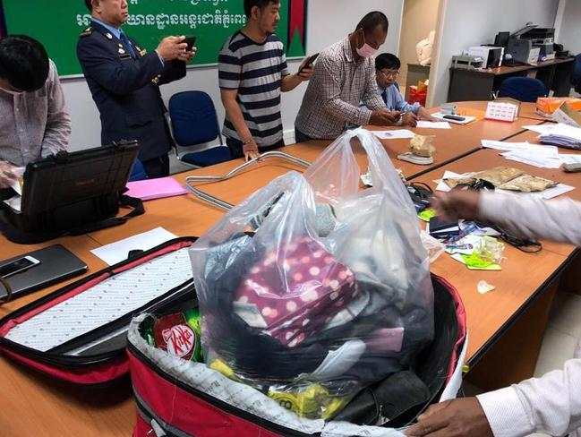 Officials inspect the suspicious parcels removed from Ms Tran's suitcase. Picture: Khmer Immigration Department