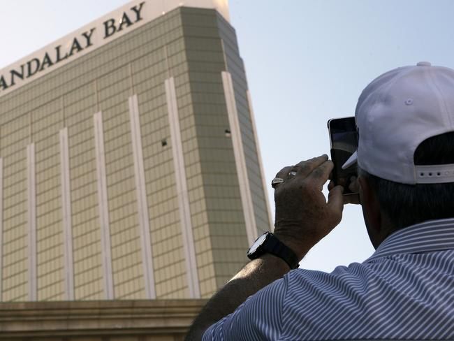 A tourist takes a photo of the broken out windows at the Mandalay Bay hotel in Las Vegas. Picture: AP