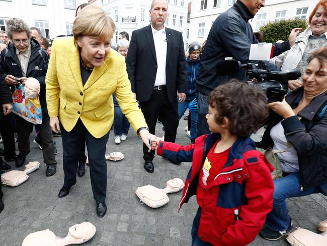 German Chancellor Angela Merkel shakes hands with a child as she visits a booth of the German Red Cross staging an information campaign on resuscitation emergency procedures. Picture: AFP