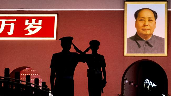 Saluting Chariman Mao ... Chinese Paramilitary police officers salut as they stand guard below a portrait of the late leader Mao Zedong in Tiananmen Square on June 4, 2014 in Beijing, China. Picture: Kevin Frayer/Getty Images