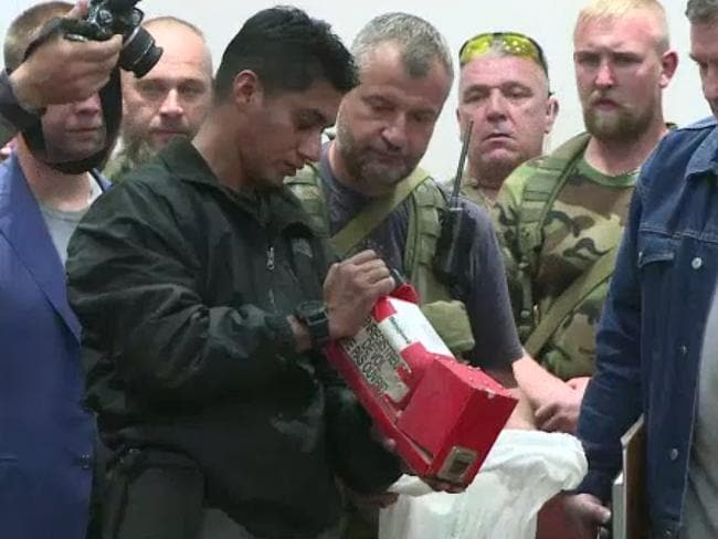 Extra care ... A Malaysian official checking one of the two black boxes recovered from the crash site of the MH17 jet.