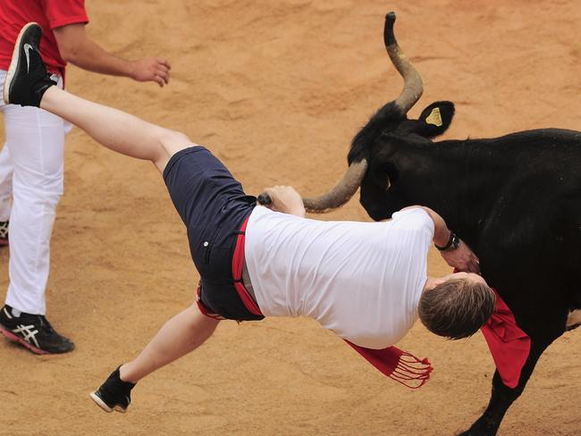 A reveler is pushed by a cow in the bull ring, at the San Fermin festival, in Pamplona, Spain, Monday, July 14, 2014. Revelers from around the world arrive to Pamplona every year to take part in some of the eight days of the running of the bulls. (AP Photo/Alvaro Barrientos)