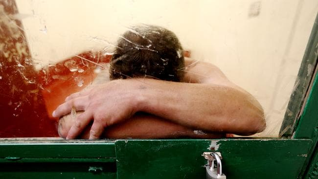 A man rests his head againt the door of his ice holding cell at Sydney's Surry Hills police station. Picture: Adam Taylor