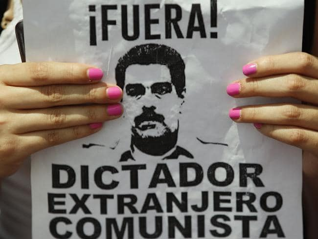 An anti-government protester holds a sign with a photo of President Nicolas Maduro and a message that reads in Spanish: Out! Dictator, Foreigner, Communist during a women's march against repression in Caracas on Saturday. Picture: Ariana Cubillos/AP