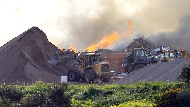 A front end loader and trucks work next to the timber and mulch fire at a recycling depot at a Wingfield dump. Picture: Campbell Brodie