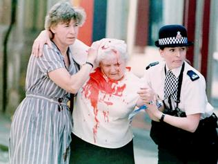 IRA bomb explosion in Manchester, Great Britain - unidentified woman covered in blood being helped away from scene of bomb blast, Jun 1996. /Bomb/explosions/Overseas