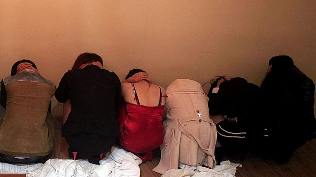 Sex workers crouch by a wall during the police raid in Dongguan's entertainment quarter. Picture: AFP