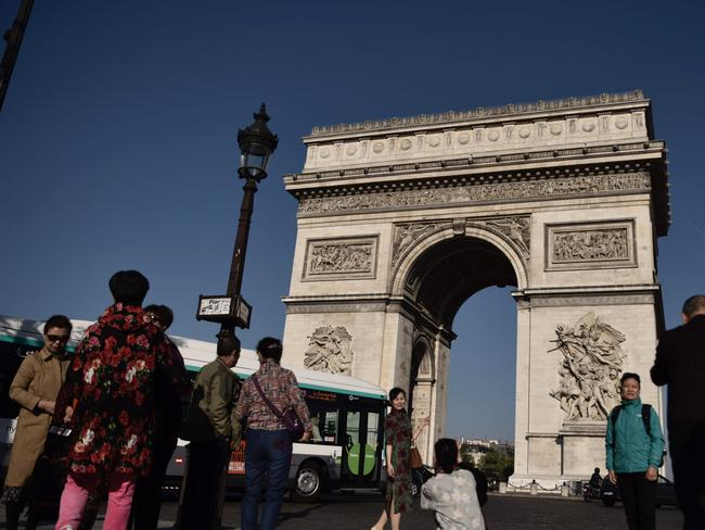 Tourists take pictures near the Arc de Triomphe monument a day after a gunman opened fire there.