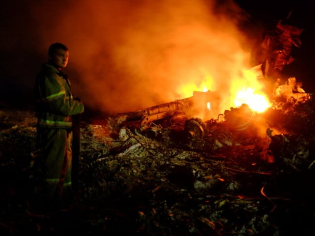 Fireball ... A firefighter stands as flames burst among the wreckages of the Malaysian airliner MH17 after it crashed near the town of Shaktarsk. Picture: Dominique Faget