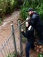 Jess Libbis and Troy Peck check the flow of Brownhill Creek at Torrens Park. Picture: Campbell Brodie